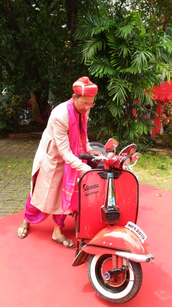 Sanjeev Bhiwandkar stands smiling before his shining red limited edition 4-Speed 1963 Vespa