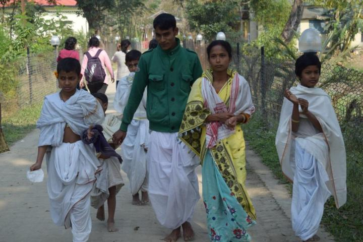 Family in traditional dress coming out of a satra in Majuli, Assam
